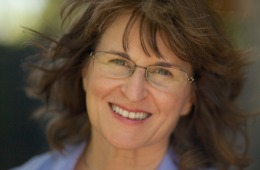 Photograph of Karla - a smiling white middle-aged female with brown hair and glasses