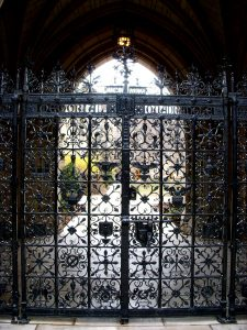 Photo of a decorateive wrought iron gate set in a rock frame