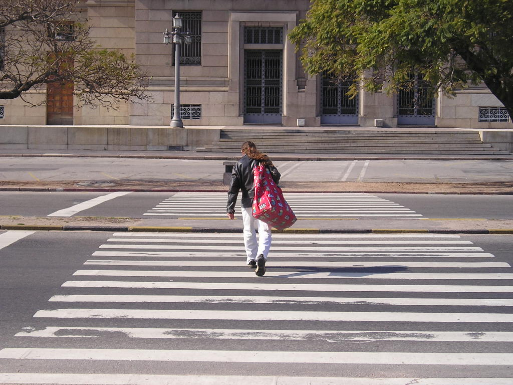 Man walking in crosswalk with bulky bag on his shoulder