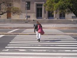 Man walking in crosswalk with bulky bag on his shoulder