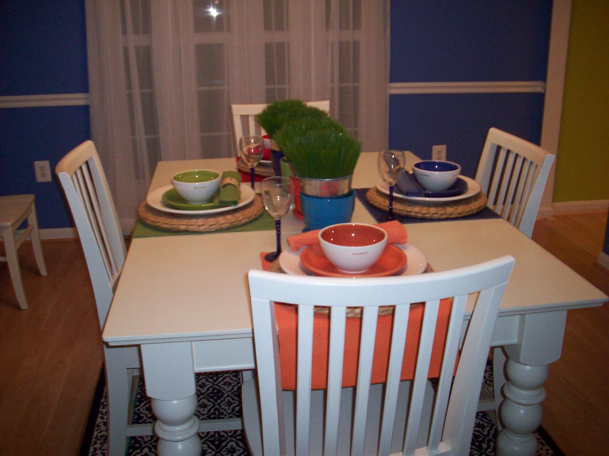 Photo of a suqare table with a white table cloth and different colored place settings. No one is sitting at the table.