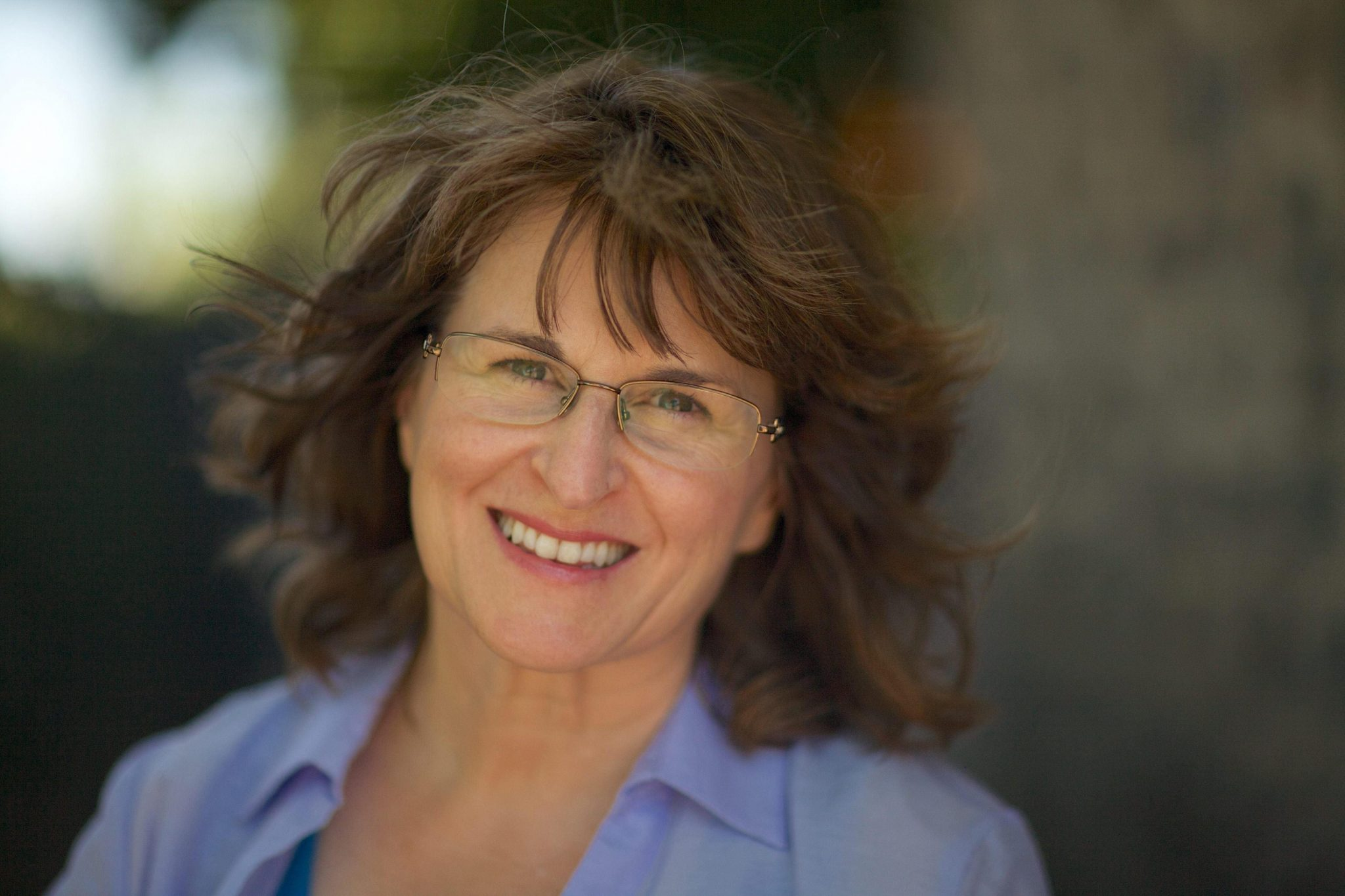 Photo of Karla McLaren, a white middle aged person with brown wavy hair, green eyes, and glasses