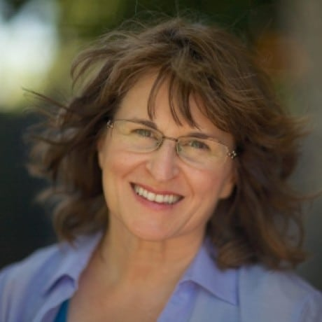 Photo of Karla McLaren, a smiling middle-aged white woman with wavy brown hair, green eyes, and glasses.